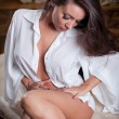 Young beautiful sexy woman in white shirt posing challenging indoor .Sexy brunette Woman with White men's shirt posing in vintage room .Attractive women sitting on old chair — Stock Photo #27278239