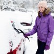 Young woman remove snow from car — Zdjęcie stockowe #25791161
