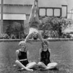 Acrobat balancing on womens shoulders — Stock Photo #12290205