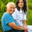 Smiling elderly woman outdoors with doctor / nurse — Stock Photo #13854258