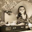 Baby girl sitting into the old suitcase — Stock Photo #14734925