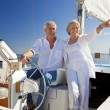 A happy senior couple sitting at the wheel of a sail boat — Stock Photo #21588565