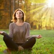 Beautiful young girl meditating in autumn park — Стоковое фото #37342721