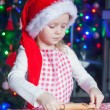 Adorable little girl in Santa hat baking gingerbread Christmas cookies at home — Stock Photo #37844801