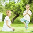 Yoga in park. mother and son — Stock Photo #31114259