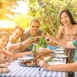 Group of happy friends eating and toasting at garden barbecue - Concept of happiness with young people at home enjoying food together — Stock Photo #50208815