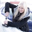 Young unhappy woman scraping ice from car — Stock Photo #39661271