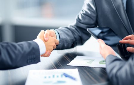 Business shaking hands in office