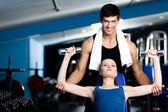 私人教练帮助女人若行使与重量