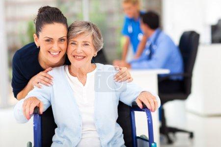 adult daughter accompanying senior mother visiting doctor