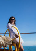 Attractive asian girl sailing on a yacht on summer day