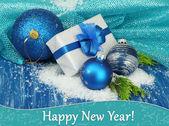 作文与圣诞球、 礼品盒和彩色木制背景上雪