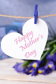 Happy Mothers Day message written on paper heart with flowers on purple background