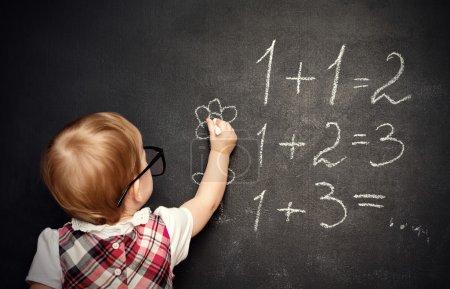 宝贝女孩小学生绘制一支粉笔在黑板上