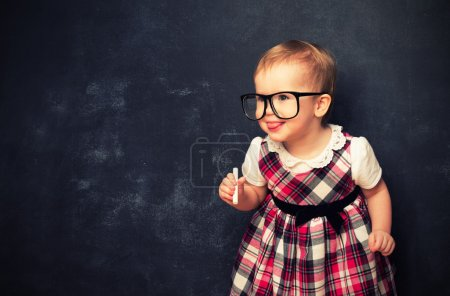 Funny baby girl  in glasses and chalk at a school board