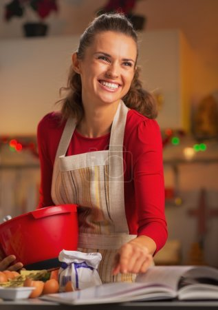 快乐的年轻家庭主妇在厨房里准备圣诞大餐_高清图片_邑石网