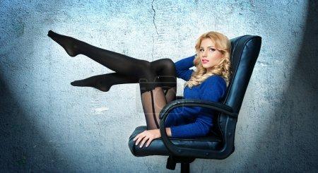 有吸引力的性感金发女性,明亮的蓝色衬衫和黑色的长筒袜,构成微笑着坐在办公椅上。长长的腿,在蓝色-工作室拍摄的性感的金发女人的画像_高清图片_邑石网