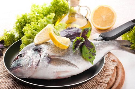 Fresh fish of dorado on a frying pan with a lemon and olive oil
