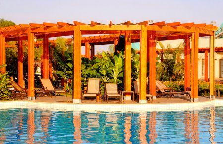 Resort swimming pool, wood pergola and deck chairs