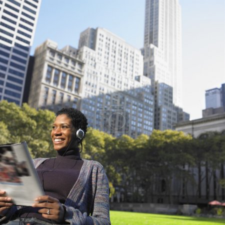 女子在公园阅读杂志时听音乐