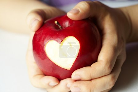 Hand with apple, which cut heart