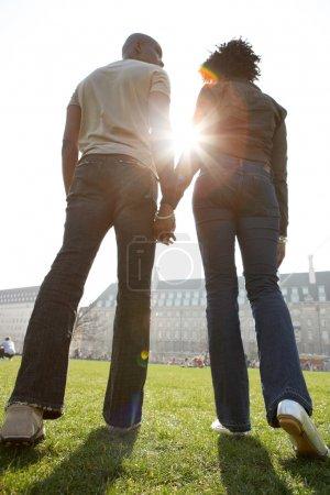 后方的看法,男人和女人的数字手牵着手走过伦敦市阳光明媚的日子时._高清图片_邑石网