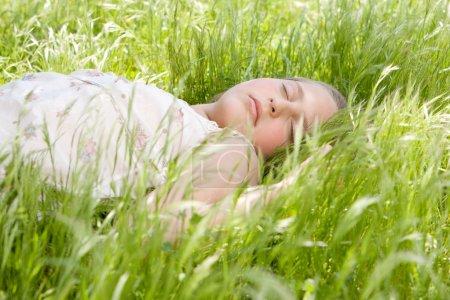 关门的美丽年轻的金发女孩睡在园中的长长的绿草上._高清图片_邑石网
