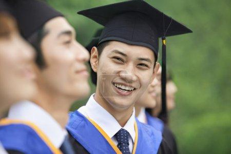 在一排的年轻的大学毕业生中微笑的人_高清图片_邑石网