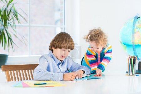 学校男孩做他的作业,他蹒跚学步的姐姐看着他